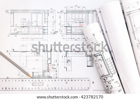 architectural blueprints and blueprint rolls with pencil and ruler - stock photo