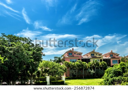 Architectural buildings along a street in Florida blue sky background  Street view of Real estate residential buildings with palms and trees in vacation travel destination, filtered image - stock photo