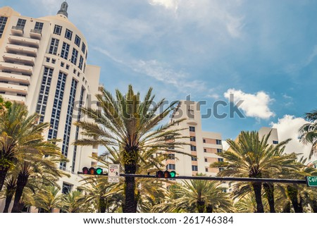 Architectural buildings Miami Style South Beach Florida image retro filtered   Modern residential skyscraper buildings art deco with palm trees in Miami against blue tropical sky background - stock photo