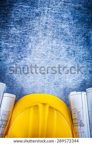 Architectural construction drawings with protective hard hat on silver-metal vintage scratched background maintenance concept. - stock photo