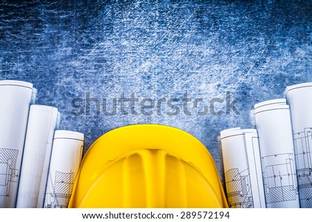 Architectural construction plans with building helmet on silver-metal vintage scratched background maintenance concept. - stock photo