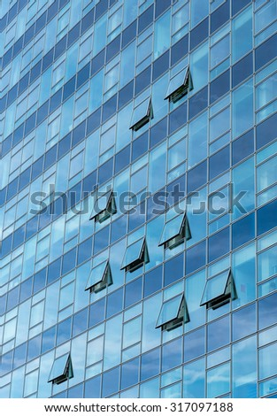 Architectural detail of a modern blue glass skyscraper building with open windows