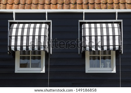 Architectural detail of a typically Dutch wooden house's windows with awnings. - stock photo
