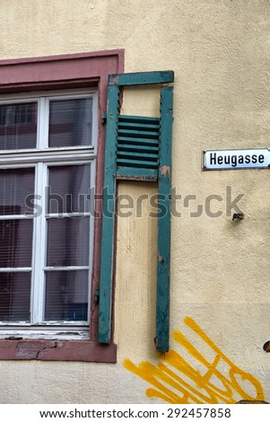 Architectural Detail of Building in Disrepair, Close Up of Window with Broken Shutter and Yellow Graffiti Spray Painted on Wall on Heugasse Street - stock photo