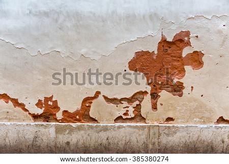 Architectural Detail of Chipped Wall - Red Stone Wall Painted White with Large Erosed Chips and Cracks in Surface - stock photo
