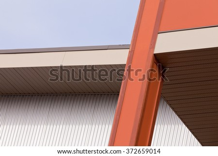 Architectural detail on a metal clad building exterior with the support of an extension creating an angle against a clear blue sky - stock photo
