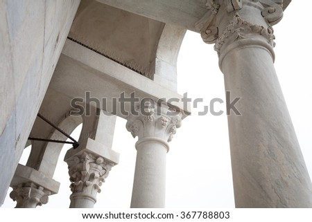 Architectural detail with columns and arches of the small loggia located in the top of the leaning tower of Pisa, Italy.