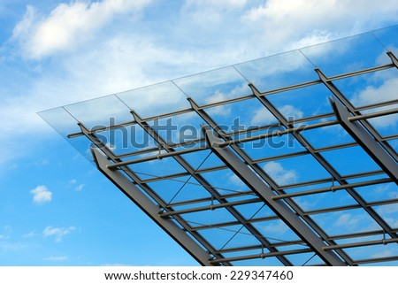 Architectural Details of a Glass and Steel Building / Detail of steel and glass roof of a modern building with blue sky and clouds - stock photo