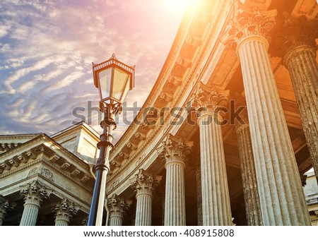 Architectural ensemble of Kazan Cathedral in Saint Petersburg, Russia - columns and metal lantern against dramatic sunset sky with bright sunlight - stock photo