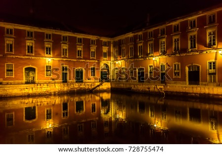 Architectural landmark Lisbon Portugal Europe renovated ship building building at night with reflection on water