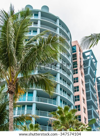 Architectural luxury building Miami Style South Beach Florida USA.  Modern residential buildings blue and apricot color with palm trees in Art-Deco district against blue sky background - stock photo