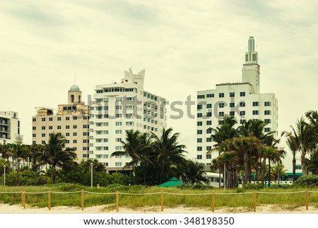 Architectural luxury building Miami Style South Beach Florida USA.  Modern white residential buildings with palm trees against cloudy sky background. Image is filtered for instagram look - stock photo