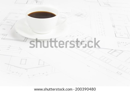 Architectural office desk with blueprints and coffe cup. - stock photo