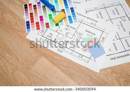 architectural plan of the house, color palette, furniture and fabric samples on wooden table - stock photo