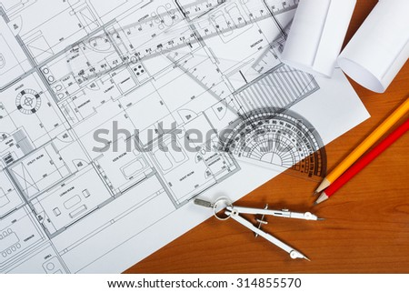 Architectural plans, pencils and ruler on the desk - stock photo