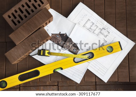 Architectural project and construction's tools on brown clinker brick background