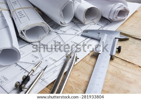 Architectural project, blueprints, blueprint rolls and  divider compass, calipers on vintage wooden background. Construction concept. Engineering tools. Copy space - stock photo