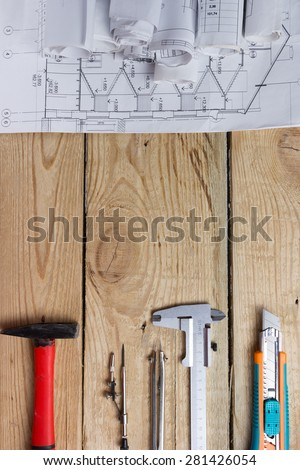 Architectural project, blueprints, blueprint rolls and hammer, divider compass, calipers, model knife on vintage wooden background. Construction concept. Engineering tools top view. Copy space - stock photo