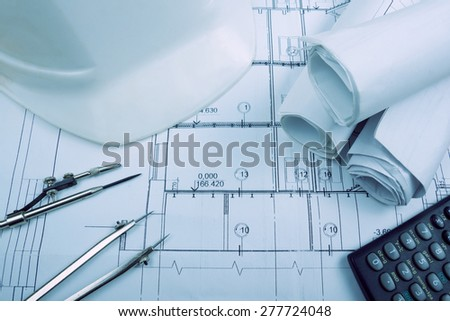 Architectural project, blueprints, blueprint rolls, compass divider, calculator, white safety on plans. Engineering tools view from the top. Copy space. Construction background. Blue toned - stock photo