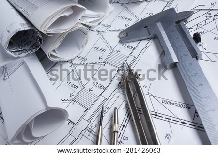 Architectural project, blueprints, blueprint rolls, compass divider, calculator, white safety on plans. Engineering tools view from the top. Copy space. Construction background