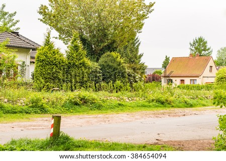 Architectural single-family houses with hedges and trees in Germany  Typical German street with detached houses against cloudy sky background, image for real estate business blog magazine book cover