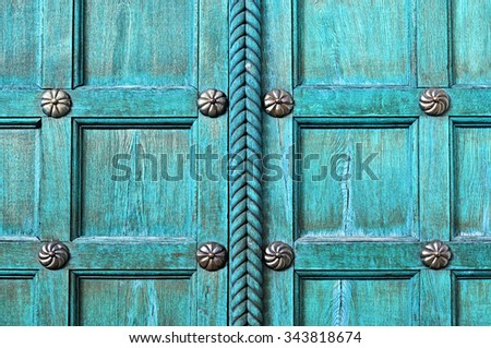 Architectural textured background - old wooden turquoise door  with metal bronze rivets on the old wooden textured surface - stock photo