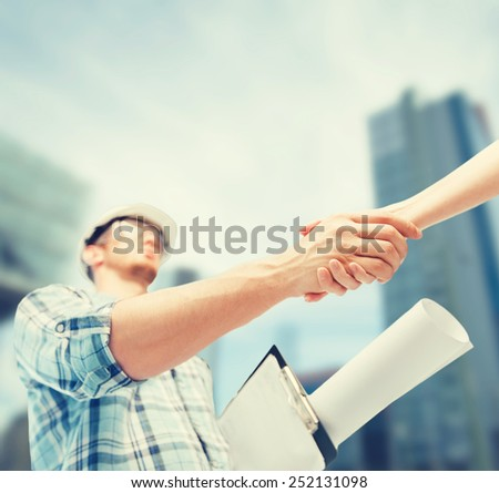 architecture and home renovation concept - builder with blueprint shaking partner hand - stock photo