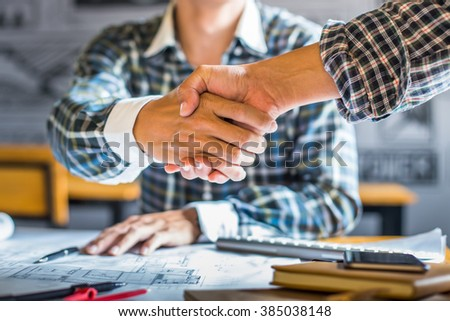 architecture and home renovation concept - builder with blueprint shaking partner hand in retro style. - stock photo