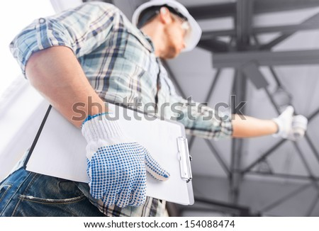 architecture and home renovation concept - man in helmet and gloves with blueprint in factory - stock photo