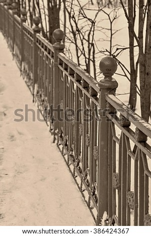 architecture and part of an old iron fence in vintage style of winter park of tone sepia