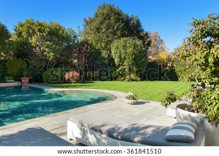 Architecture; beautiful garden with pool, two sunbeds view - stock photo