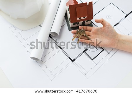 architecture, building, construction, real estate and home concept - hand with house keys and blueprint - stock photo