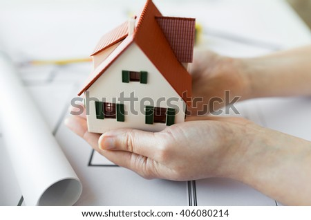 architecture, building, construction, real estate and people concept - close up of architect hands holding living house model above blueprint on table - stock photo