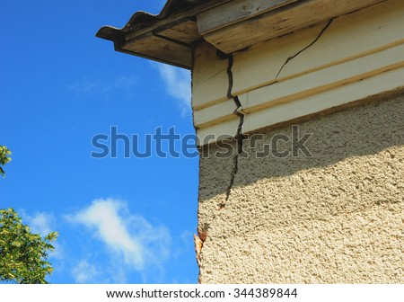 Architecture detail of damaged house corner dilapidated old building facade wall over blue sky background. Private abandoned home fall to ruin. Exterior House - stock photo