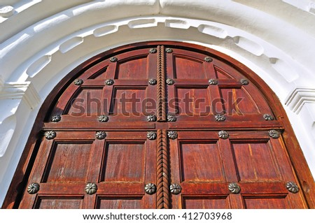 Architecture detailed background - aged wooden door of mahogany color with metal rivets and upper arch of white stone - vintage architecture background - stock photo