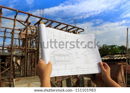architecture drawings in hand on house building background with blue sky