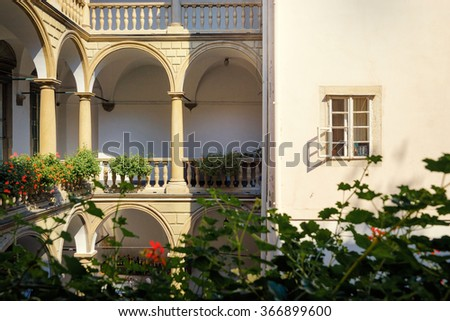 Architecture. Facade of beautiful building with column and balconies, and flowers on it. - stock photo