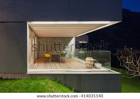Architecture modern design, concrete house, lit terrace at night - stock photo
