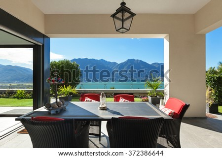 Architecture, nice porch with table and chairs, lake view - stock photo