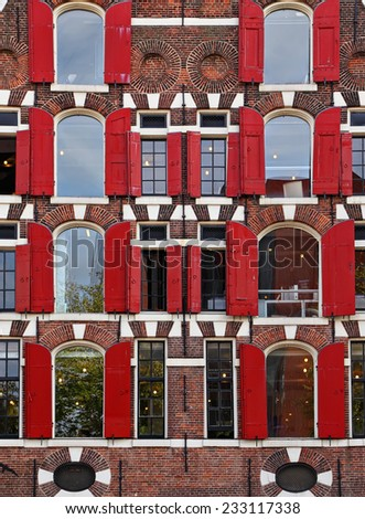 Architecture of ancient classic dutch building (Amsterdam) - Brick wall with red blinds (shutters) windows background - stock photo