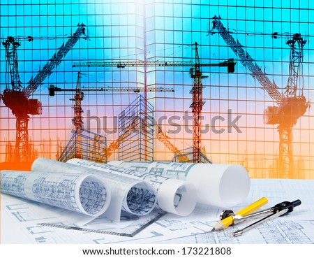 architecture plan on architect working table with building and reflection of crane construction on mirror building - stock photo