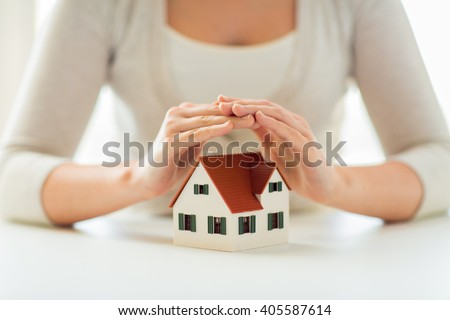 architecture, safety, security, real estate and property concept - close up of hands protecting house or home model - stock photo