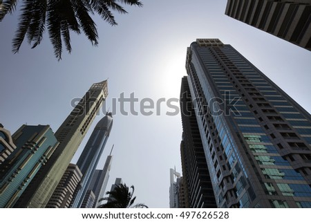 Architecture theme. Corporate buildings in perspective. Futuristic architecture. Skyscrapers pointing to the sun. Financial center. Metro station. Blue sky. Futuristic oasis of the future.