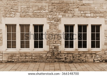 Architecture View of Windows and the Exterior of an Old Stone Building in Sepia - stock photo