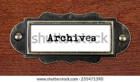 Archives - file cabinet label, bronze holder against grunge and scratched wood  - stock photo