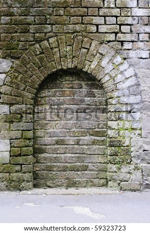Archway in a brick stone wall - stock photo