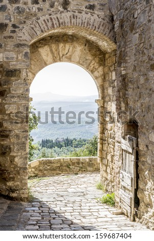 Archway in San Quirico with view to the Tuscan landscape in Tuscany, Italy - stock photo