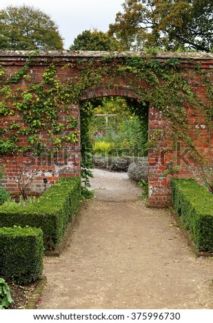 Archway into an english walled garden with Box hedging - stock photo