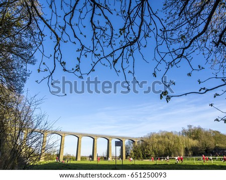 Archways of roman viaduct framed by tree branches near Chirk with blue sky in Wales, UK