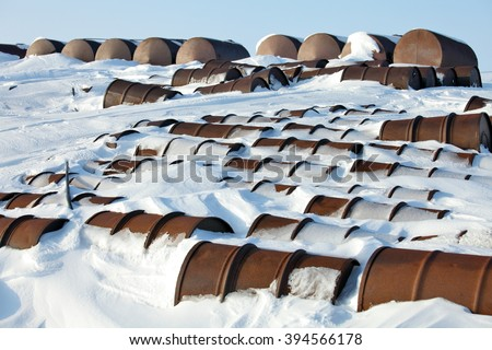 Arctic coast pollution. Rusting discarded oil barrels, oil drums in the arctic snow near abandoned polar settlements and stations